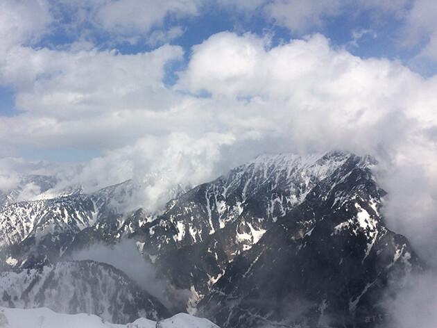 大観峰から雲の隙間に望む山々